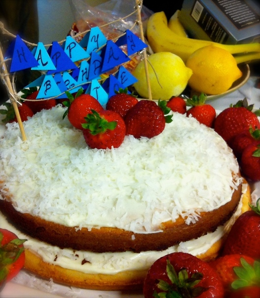 Coconut cake with lemon zest, mascarpone frosting, topped with stawberries.